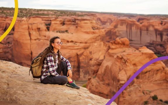a girl sitting on a canyon edge