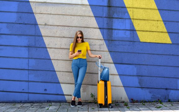 Young Woman With Luggage Using Mobile Phone While Standing Against Wall