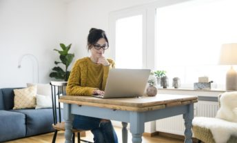 Woman sitting at table using laptop