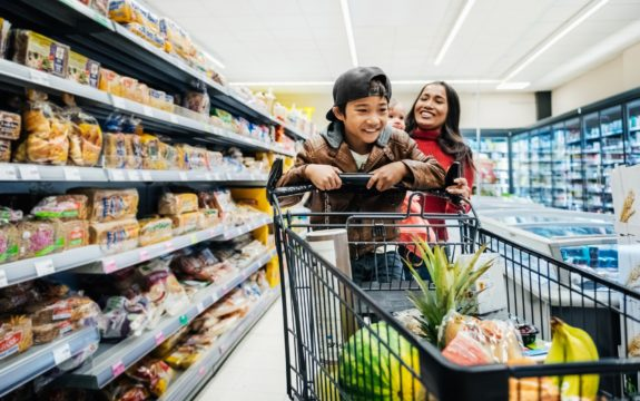 A young boy having fun on a shopping cart while out buying groceries with his family.