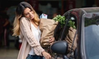 Woman multi-tasking getting in the car after shopping at the grocery store